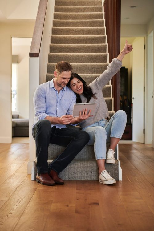 woman celebrating besides man looking at tablet