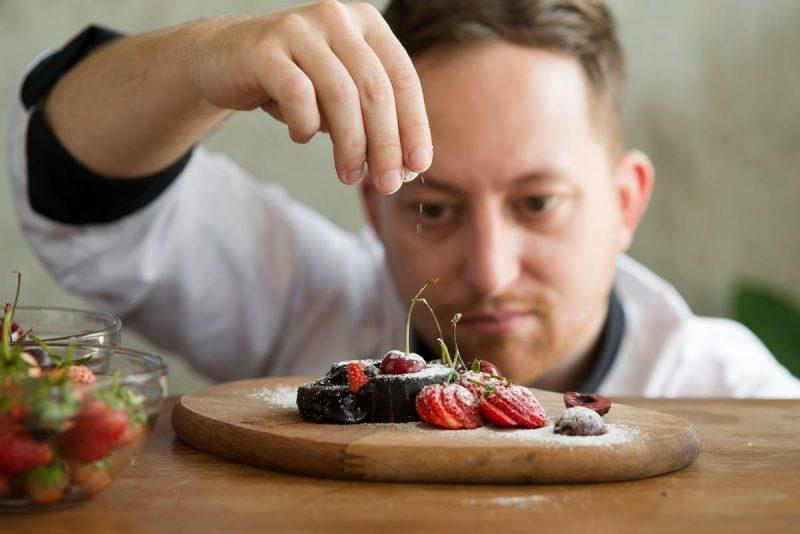 un chef pâtissier confectionnant un dessert